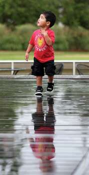 Jayson Guerra, 2, of Katy, looks up as a bolt of lightning streaked through the sky as he walked in the sprinkles after rain showers fell during Bayou Shuttle's monthly Kayak Camp at Discovery Green,  Sunday, Aug. 5, 2012, in Houston. Kayak Camp is the first Sunday of every month. Photo: Karen Warren, Houston Chronicle / © 2012  Houston Chronicle