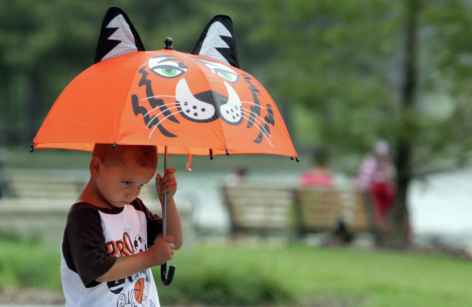 Xandric Perry, 3, frowns as he walks out of Houston Zoo with his grandparents as dark clouds moved into the area. Photo: Mayra Beltran / © 2012 Houston Chronicle