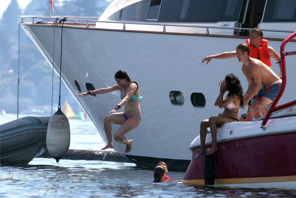 A boater leaps into the water from a boat on the Log Boom during Seafair on Sunday, August 5, 2012 on Lake Washington.