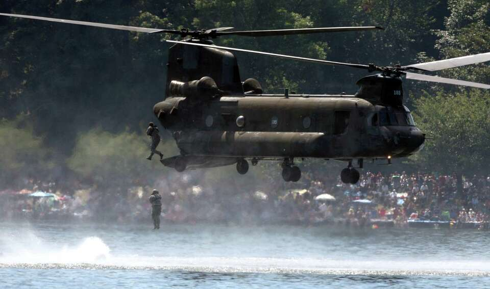 Special Forces members leap from a CH-47 helicopter during a demonstration at Seafair on Sunday, Aug