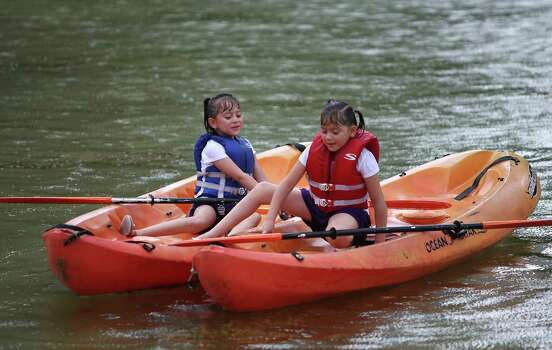 Katherine Mercado,in the blue life jacket, left,  7, of Hermosillo, Sonora, Mexico, tries to keep her twin sister, Nahomy, also 7, out of her kayak as they navigate their kayaks during rain showers that fell during Bayou Shuttle's monthly Kayak Camp at Discovery Green,  Sunday, Aug. 5, 2012, in Houston. Kayak Camp is the first Sunday of every month. Photo: Karen Warren, Houston Chronicle / © 2012  Houston Chronicle