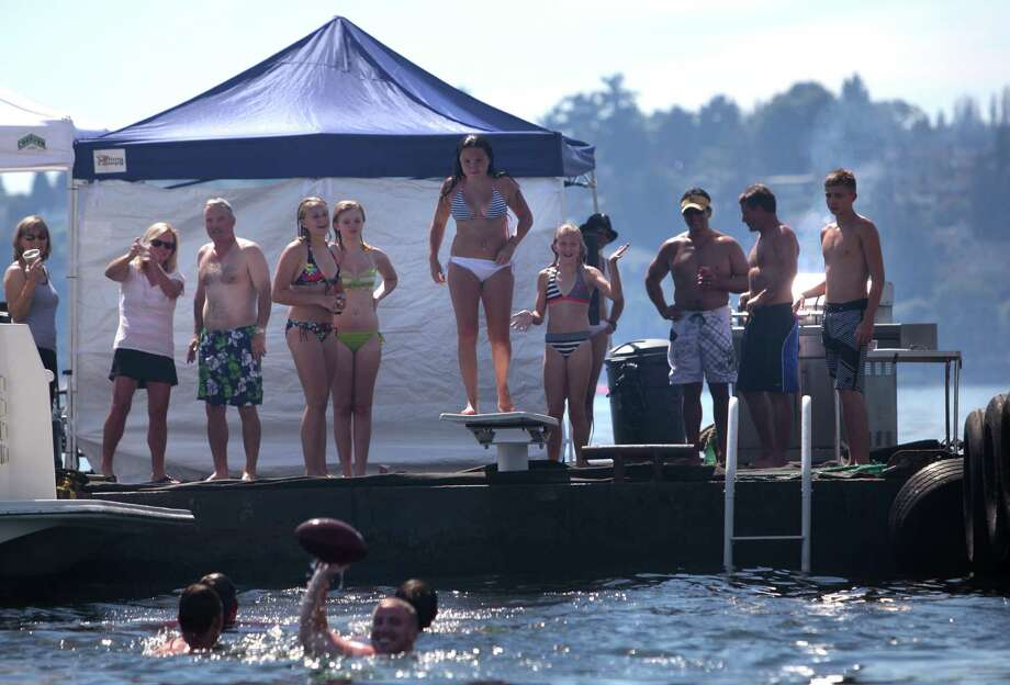 People jump off a diving board into Lake Washington from the Log Boom during Seafair on Sunday, August 5, 2012 on Lake Washington. Photo: JOSHUA TRUJILLO / SEATTLEPI.COM