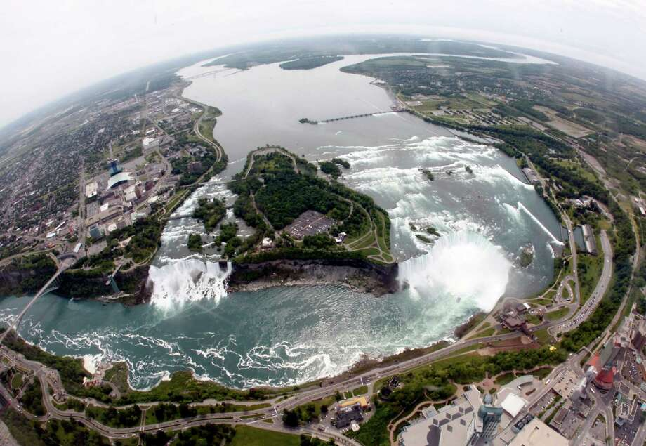 FILE - In this June 3, 2009 photo, Ruedi Hafen, not shown, president and chief pilot of Niagara Helicopters Ltd., flies over Niagara Falls in Niagara Falls, Ontario. In recent years, for economic reasons, Niagara Falls has thrown open its doors to casino gambling, gay weddings and a tightrope walk that, until laws were relaxed, would have meant arrest. It even briefly considered taking in toxic wastewater from hydraulic fracturing. On the drawing board now is a plan to entice young people to move in by paying down their student loans. (AP Photo/David Duprey, File) Photo: David Duprey