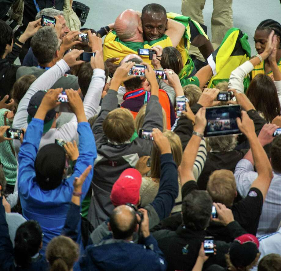 Jamaica's Usain Bolt, top, celebrates with the crowd after the men's 100-meter final Sunday. Countryman Johan Blake took home the silver medal, and Justin Gatlin of the United States earned the bronze. Bolt, 25, goes for the 200-meter gold this week. Photo: Smiley N. Pool / © 2012  Houston Chronicle