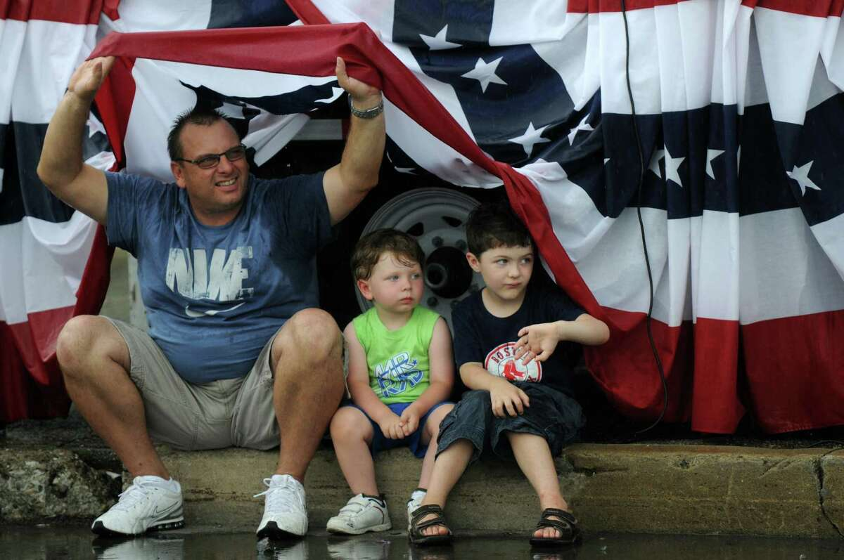 Timothy Grolley of St. Petersburg, Florida tries to stay under dry under the flag festooned reviewing stand with his grandson Lucas Grolley, 3, center, and their cousin Nicholas, 5, both of Schuylerville, as a heavy rain starts to fall on Broad Street during the 18th annual Turning Point Parade on Sunday Aug. 5, 2012 in Schuylerville, NY. Timothy grew up in Schuylerville. (Philip Kamrass / Times Union)