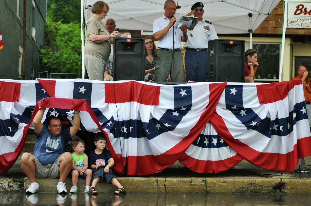 Timothy Grolley of St. Petersburg, Florida tries to stay under dry under the flag festooned reviewing stand with his grandson Lucas Grolley, 3, center, and their cousin Nicholas, 5, both of Schuylerville, as a heavy rain starts to fall on Broad Street during the 18th annual Turning Point Parade on Sunday Aug. 5, 2012 in Schuylerville, NY. Timothy grew up in Schuylerville. Parade Grand Marshall Colonel Richard Goldenberg, Joint Force HQ-New York National Guard, who served in Iraq in 2005, salutes a passing flag. (Philip Kamrass / Times Union)