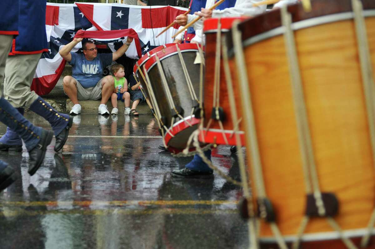 Timothy Grolley of St. Petersburg, Florida tries to stay under dry under the flag festooned reviewing stand with his grandson Lucas Grolley, 3, center, and their cousin Nicholas, 5, both of Schuylerville, as a heavy rain starts to fall on Broad Street during the 18th annual Turning Point Parade on Sunday Aug. 5, 2012 in Schuylerville, NY. Timothy grew up in Schuylerville. The Stony Creek Fife and Drum Corps of Stony Creek, CT marches past. (Philip Kamrass / Times Union)