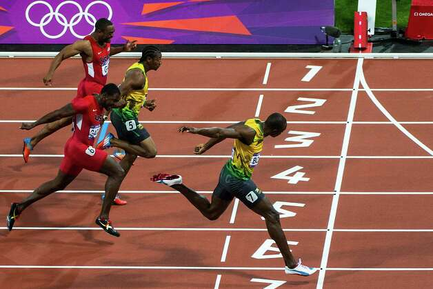 Usain Bolt of Jamaica, crosses the finish line ahead of Justin Gatlin of the USA, Yohan Blake of Jamaica, and Tyson Gay of the USA down the track during the men's 100-meter final at the 2012 London Olympics on Sunday, Aug. 5, 2012. Bolt won gold in the event, with Blake second and Gatlin taking third. ( Smiley N. Pool / Houston Chronicle ) Photo: Smiley N. Pool, Houston Chronicle / © 2012  Houston Chronicle