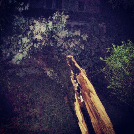 A large tree branch ripped power lines down and fell on the roof of a home at 18 Grimes Road in Old Greenwich Sunday night, Aug. 5, 2012, cutting power to the home. Photo: Contributed Photo