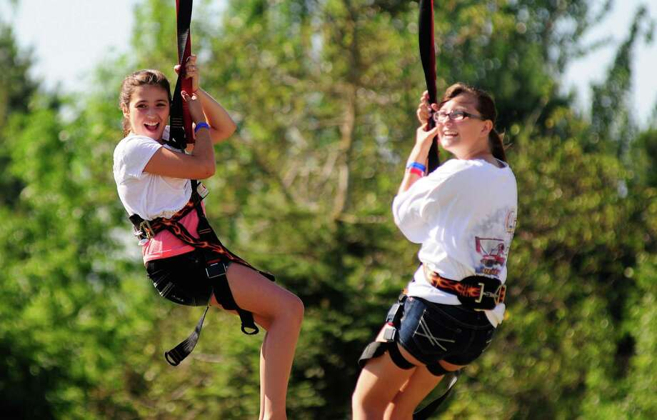 Samantha Cote, 12, and Marisa Sargent, 13, smile as they ride down a zip-line at Genesee Park. Photo: LINDSEY WASSON / SEATTLEPI.COM