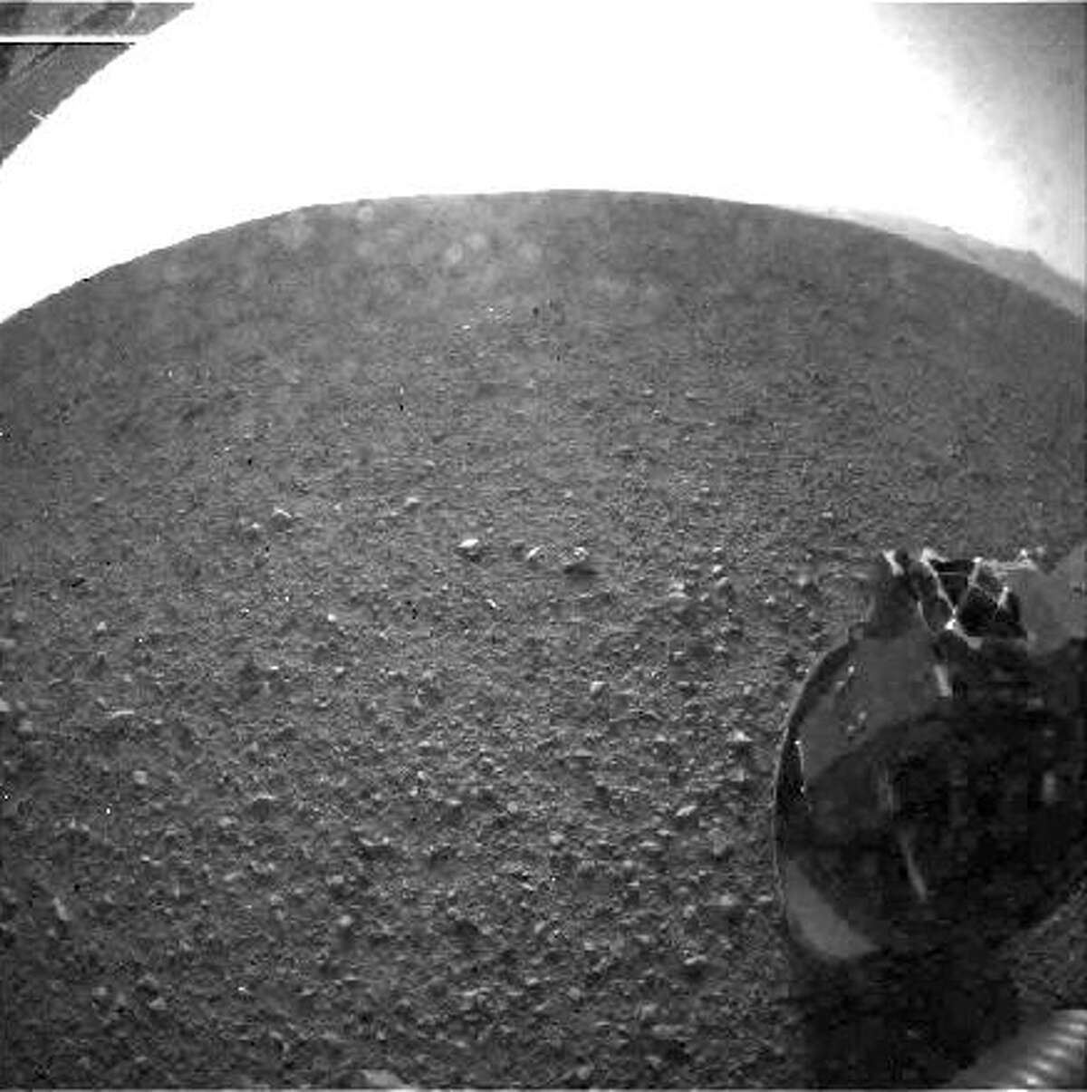 This is one of the first images taken by NASA's Curiosity rover, which landed on Mars Monday, Aug. 6, 2012, CT. The clear dust cover that protected the camera during landing has been sprung open. Part of the spring that released the dust cover can be seen at the bottom right, near the rover's wheel. On the top left, part of the rover's power supply is visible. The cameras are looking directly into the sun, so the top of the image is saturated.