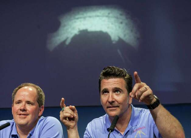 Mars Science Laboratory Curiosity Richard Cook, MSL deputy project manager, left, and Adam Steltzner, MSL entry, descent and landing (EDL) lead, right, point to the first image taken by NASA's Curiosity rover, which landed on Mars the evening of Aug. 5 on the surface of Mars, during  a news conference at NASA's Jet Propulsion Laboratory in Pasadena, Calif., Sunday, August 5, 2012. (AP Photo/Damian Dovarganes) Photo: Damian Dovarganes