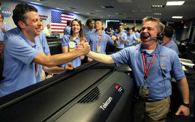 Flight director Keith Comeaux, right, celebrates with Martin Greco after a successful landing inside the Spaceflight Operations Facility for NASA's Mars Science Laboratory Curiosity rover at Jet Propulsion Laboratory  in Pasadena, Calif., Sunday, Aug. 5, 2012. The Curiosity robot is equipped with a nuclear-powered lab capable of vaporizing rocks and ingesting soil, measuring habitability, and potentially paving the way for human exploration. (AP Photo/Brian van der Brug,Pool) Photo: Brian Van Der Brug