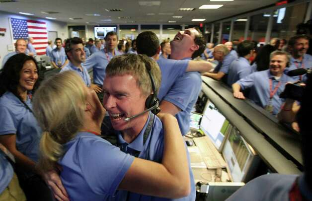 Telecom engineer Peter Llott, center, hugs a colleague to celebrate the successful landing  of NASA's Mars Science Laboratory Curiosity rover inside the Spaceflight Operations Facilityat the  Jet Propulsion Laboratory  in Pasadena, Calif., Sunday, August 5, 2012. The Curiosity robot is equipped with a nuclear-powered lab capable of vaporizing rocks and ingesting soil, measuring habitability, and potentially paving the way for human exploration. (AP Photo/Brian van der Brug, Pool) Photo: Brian Van Der Brug