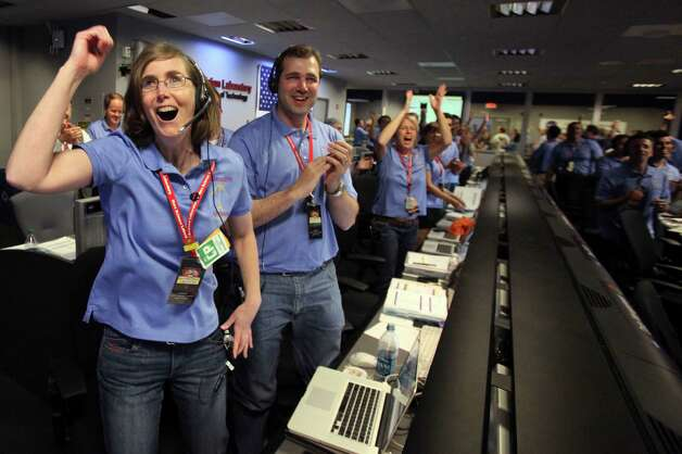 Kelley Clarke, left, celebrates as the first pictures appear on screen after a successful landing inside the Spaceflight Operations Facility for NASA's Mars Science Laboratory Curiosity rover at Jet Propulsion Laboratory  in Pasadena, Calif.,  Sunday Aug. 5, 2012. The Curiosity robot is equipped with a nuclear-powered lab capable of vaporizing rocks and ingesting soil, measuring habitability, and potentially paving the way for human exploration. (AP Photo/Brian van der Brug, Pool) Photo: Brian Van Der Brug