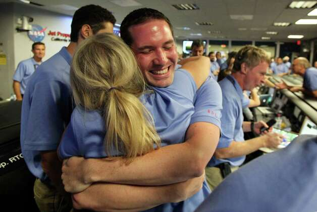 Brian Schratz hugs a colleague as he celebrates a successful landing inside the Spaceflight Operations Facility for NASA's Mars Science Laboratory Curiosity rover at Jet Propulsion Laboratory in Pasadena, Calif., Sunday Aug. 5, 2012. The Curiosity robot is equipped with a nuclear-powered lab capable of vaporizing rocks and ingesting soil, measuring habitability, and potentially paving the way for human exploration. (AP Photo/Brian van der Brug, Pool) Photo: Brian Van Der Brug
