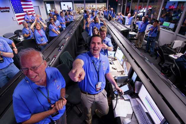 In a photo provided by NASA, the Mars Science Laboratory  team in the MSL Mission Support Area reacts after learning the the Curiosity rover has landed safely on Mars and images start coming in at the Jet Propulsion Laboratory on Mars, Sunday, Aug. 5, 2012 in Pasadena, Calif. The MSL Rover named Curiosity was designed to assess whether Mars ever had an environment able to support small life forms called microbes.  Photo Credit: (AP Photo/NASA/Bill Ingalls) Photo: NASA/Bill Ingalls