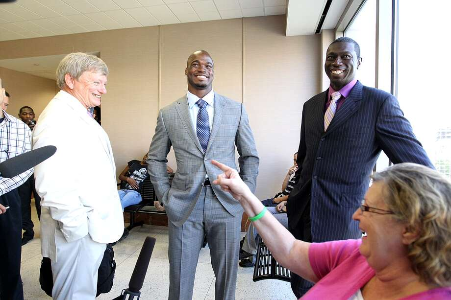 NFL player Adrian Peterson, center, waits with Rusty Hardin for Harris County Criminal Court 3 to open on Monday in Houston. Photo: Nick De La Torre, Houston Chronicle