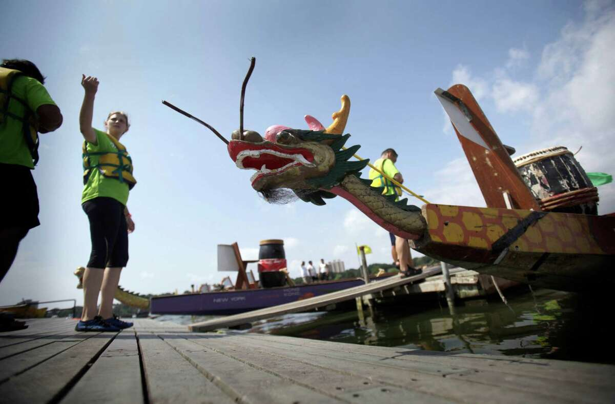 Racers board their boats during the Hong Kong Dragon Boat Festival in the Queens section of New York, Sunday, Aug. 5, 2012. The annual Hong Kong Dragon Boat Festival in Queens drew more than 180 teams Sunday, paddling aboard painted boats.