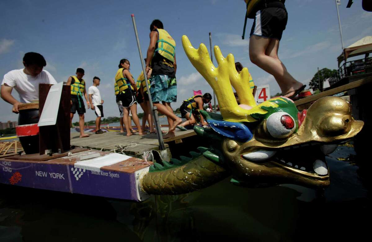 Racers board their boats during the Hong Kong Dragon Boat Festival in the Queens borough of New York, Sunday, Aug. 5, 2012.