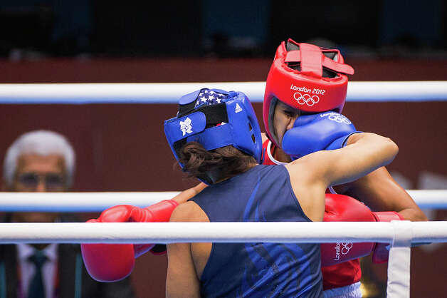 Marlen Esparza of the USA, in blue, lands a punch to the face of Venezuela's Karlha Magliocco in a women's flyweight 51-kg quarterfinal boxing match at the 2012 London Olympics on Monday, Aug. 6, 2012. With a victory in the bout, Esparza, is guaranteed of no less than a bronze medal. Photo: Smiley N. Pool, Houston Chronicle / © 2012  Houston Chronicle