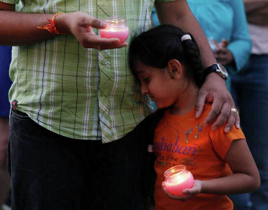 A man holds his child during a candle light vigil for the victims of the Sikh Temple of Wisconsin shooting in Milwaukee Sunday, Aug 5, 2012. An unidentified gunman killed six people at the suburban Milwaukee temple on Sunday in a rampage that left terrified congregants hiding in closets and others texting friends outside for help. The suspect was killed outside the temple in a shootout with police officers. (AP Photo/Jeffrey Phelps) Photo: JEFFREY PHELPS
