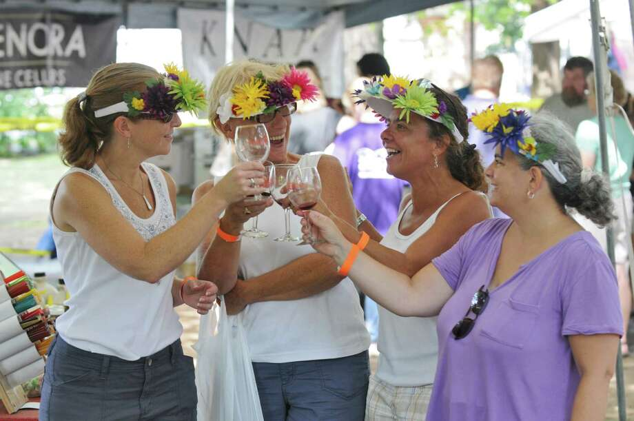 Anne Bartscherer of Manhattan, left, Betsy Hill of Ridgefield, CT, second from left, Gina Perino of Pleasantville and Pam Rotando of Ossining, right, toast each other while wearing hats made by Hill, during the Galloping Grapes benefit for the Times Union Hope Fund at the Saratoga Race Course on Sunday Aug. 5, 2012 in Saratoga Springs, NY.   The friends have been coming to the track for about a dozen years together. (Philip Kamrass / Times Union) Photo: Philip Kamrass / 00018559A