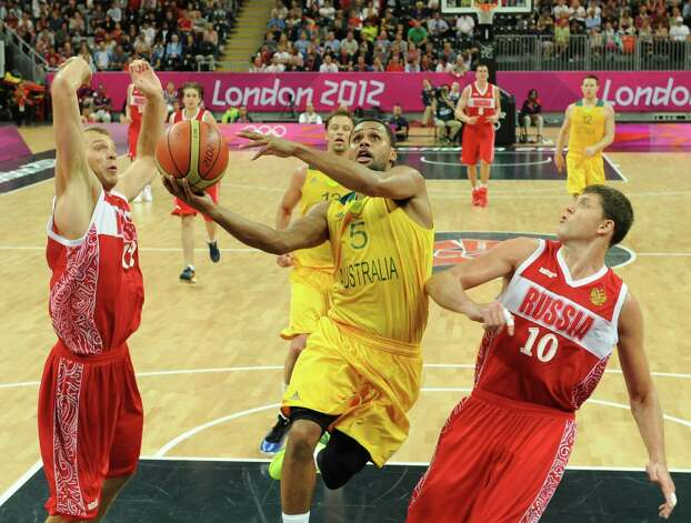 Australian guard Patrick Mills (C) jumps to score a basket despite Russian forward Victor Khryapa during the Men's Basketball Preliminary Round match as part of the London 2012 Olympic Games at the Basketball Arena on August 6, 2012 in London, England.  Australia won 82-80. AFP PHOTO POOL MARK RALSTONMARK RALSTON/AFP/GettyImages Photo: MARK RALSTON, AFP/Getty Images / AFP