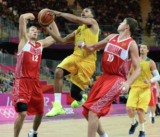 Australian guard Patrick Mills (C) jumps to score despite Russian forward Sergey Monya (L) during the Men's Basketball Preliminary Round match as part of the London 2012 Olympic Games at the Basketball Arena on August 6, 2012 in London, England.  Australia won 82-80. AFP PHOTO MARK RALSTONMARK RALSTON/AFP/GettyImages Photo: MARK RALSTON, AFP/Getty Images / AFP
