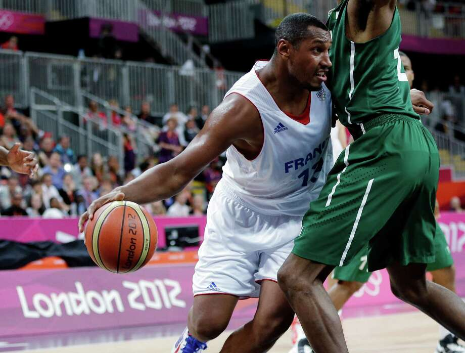 France's Boris Diaw, left, drives around Nigeria defender Alade Aminuduring, right, during a preliminary men's basketball game at the 2012 Summer Olympics, Monday, Aug. 6, 2012, in London. (AP Photo/Eric Gay) Photo: Eric Gay, Associated Press / AP
