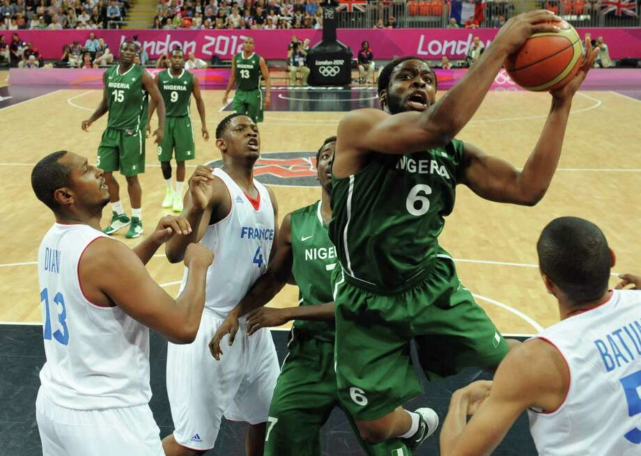 Nigerian forward Ike Diogu, second from right, jumps to score a basket eyed by French center Kevin Seraphin, second from left, and forward Boris Diaw, left, during a men's basketball preliminary round match at the 2012 Summer Olympics on Monday, Aug. 6, 2012, in London.  (AP Photo/Mark Ralston, Pool) Photo: Mark Ralston, Associated Press / Pool AFP