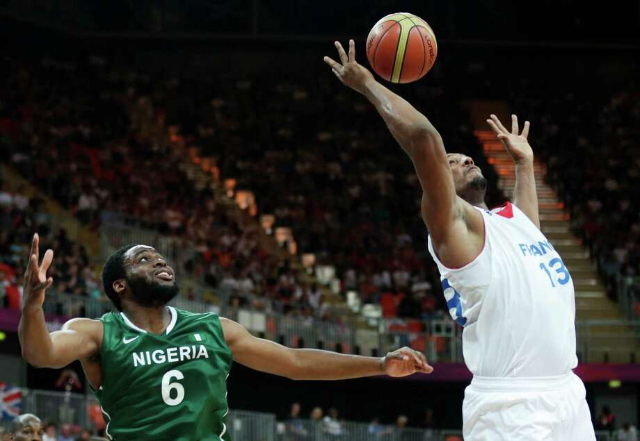 France's Boris Diaw, right, leaps up for a rebound against Nigeria's Ike Diogu during a men's basketball game at the 2012 Summer Olympics, Monday, Aug. 6, 2012, in London. (AP Photo/Charles Krupa) Photo: Charles Krupa, Associated Press / AP