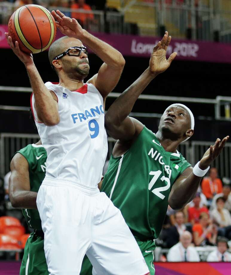 France's Tony Parker looks to pass while being defended by Nigeria's Ejike Ugboaja during a men's basketball game at the 2012 Summer Olympics, Monday, Aug. 6, 2012, in London. (AP Photo/Charles Krupa) Photo: Charles Krupa, Associated Press / AP