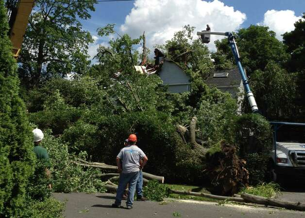 A tree crew cleans up after a downed tree on Wahneta Road in Old Greenwich. Photo: Lisa Chamoff / Greenwich Time