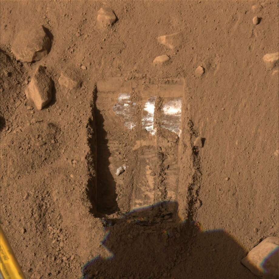 "This color image released by NASA and acquired by NASA's Phoenix Mars Lander's Surface Stereo Imager on Friday, June 13, 2008, shows one trench informally called ""Dodo-Goldilocks"" after two digs on June 12, by Phoenix's Robotic Arm. Shallow trenches excavated by the lander's backhoe-like robotic arm have turned up specks and at times even stripes of mysterious white material mixed in with the clumpy, reddish dirt. (AP Photo/NASA/JPL/CalTech)"
