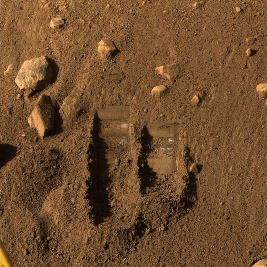 "In this photo released by NASA and taken by the Phoenix Mars Lander's surface stereo imager on Saturday, June 8, 2008, the two trenches dug by Phoenix's robotic arm are shown on the surface of Mars. Soil from the right trench, informally called ""Baby Bear, "" was delivered to Phoenix's Thermal and Evolved-Gas Analyzer or TEGA, on June 6. The following several days included repeated attempts to shake the screen over TEGA's oven number 4 to get fine soil particles through the screen and into the oven for analysis. (AP Photo/NASA/JPL/CalTech)"