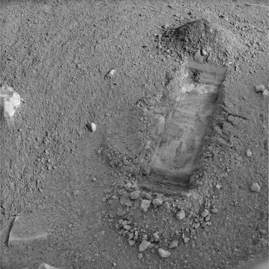 "This image released by NASA and acquired by NASA's Phoenix Mars Lander shows a new trench called ""Snow White, "" in a patch of Martian soil near the center of a polygonal surface feature nicknamed ""Chesire Cat."" Excavation near Mars' north pole was halted Wednesday as engineers fixed a glitch on the Phoenix lander that caused the partial loss of science data. (AP Photo/NASA/JPL/CalTech)"