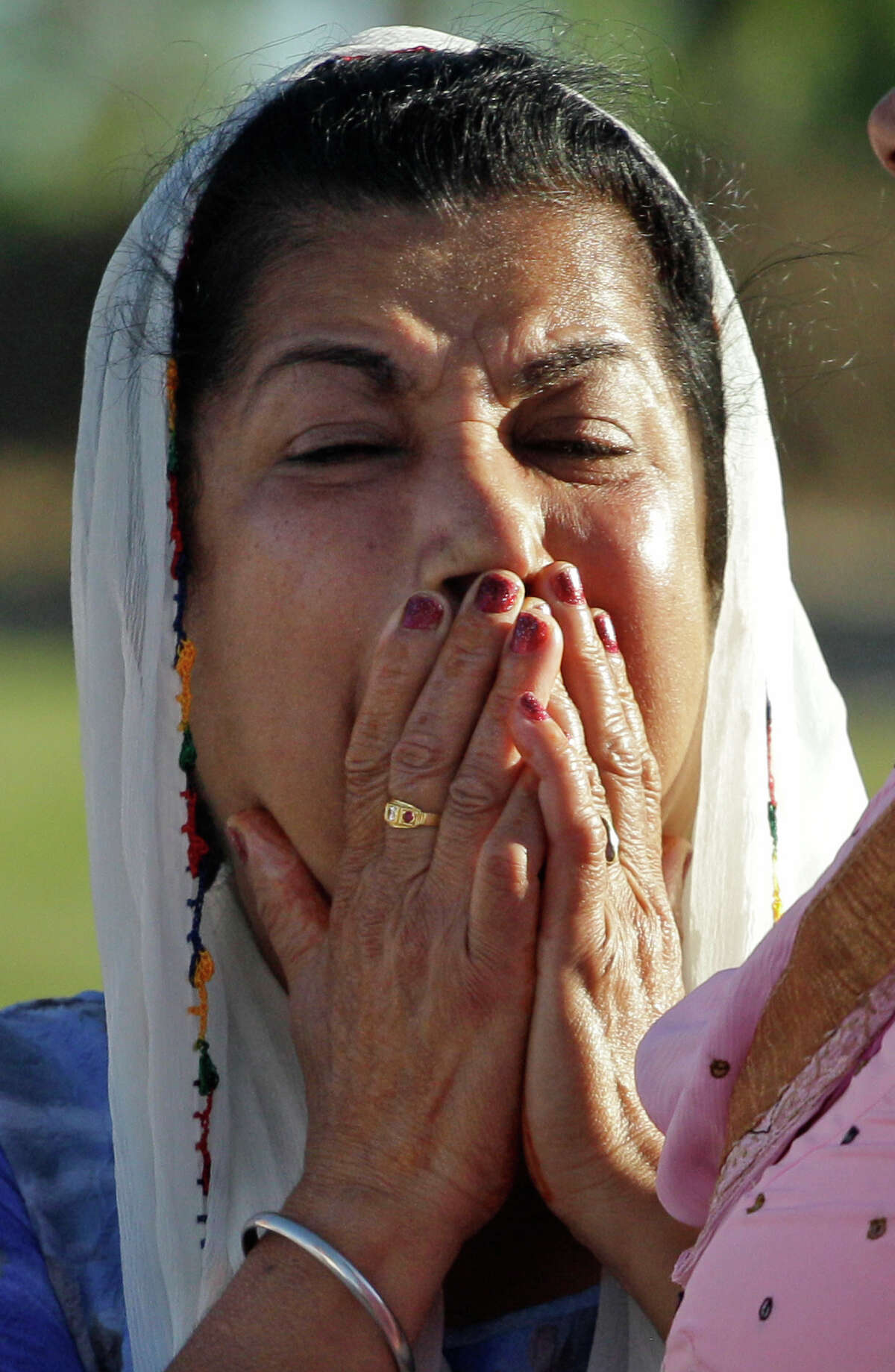 A member of the Sikh Temple of Wisconsin weeps Monday, Aug. 6, 2012, in Oak Creek, Wis., where a gunman killed six people a day earlier, before being killed himself in a shootout with police. Satwant Kaleka, 65, founder and president of the temple, died in the shooting. He was among four priests who died.