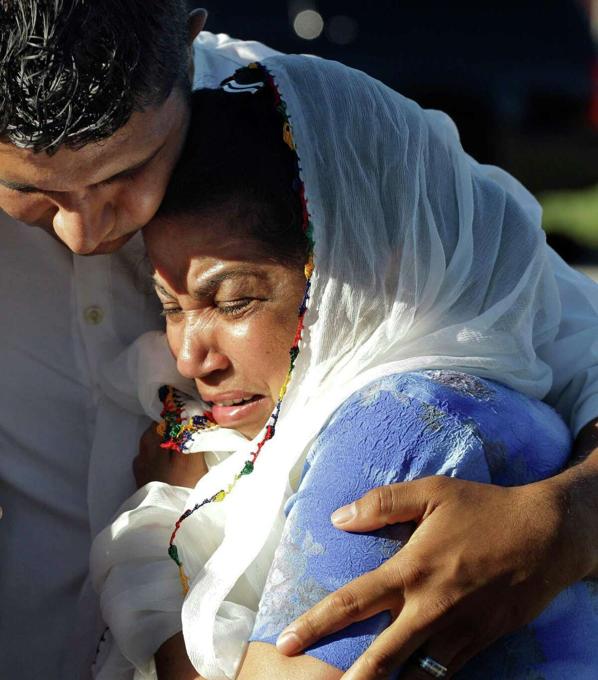 Amardeep Kaleka, son of the president of the Sikh Temple of Wisconsin, left, comforts members of the temple, Monday, Aug. 6, 2012, in Oak Creek, Wis., where a gunman killed six people a day earlier, before being shot and killed himself by police. Satwant Kaleka, 65, founder and president of the temple, died in the shooting. He was among four priests who died.