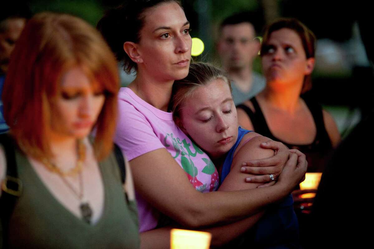 Erica Erickson, center, hugs her sister, Suzanne Best, at a candlelight vigil for the victims of the Sikh Temple of Wisconsin shooting, Sunday, Aug. 5, 2012, at Cathedral Square in Milwaukee. A gunman killed six people at the suburban Milwaukee temple on Sunday in a rampage that left terrified congregants hiding in closets and others texting friends outside for help. The suspect was killed outside the temple in a shootout with police officers. (AP Photo/Milwaukee Journal-Sentinel, Chris Wilson)