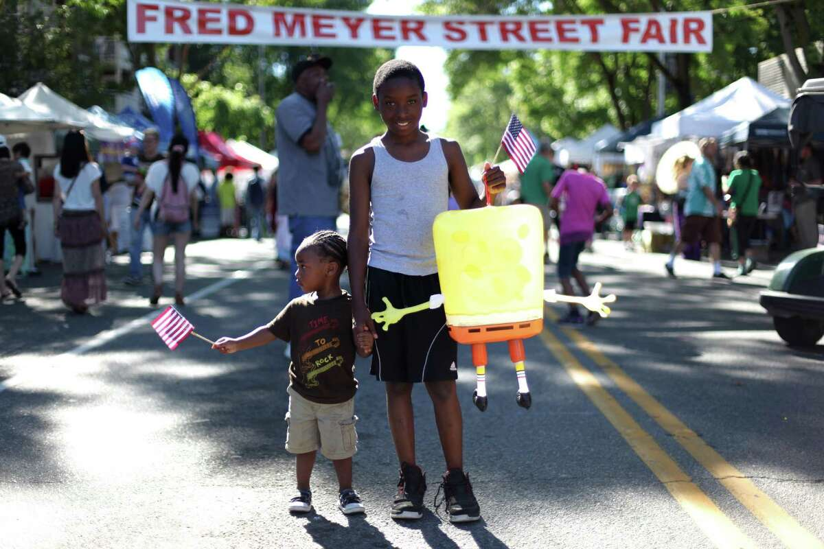 Raythel Thompson, 12, and Maiking Newton, 1, take in the scene on NE 125th Street during Lake City's 70th annual Pioneer Days festival. The annual festival includes a street fair, salmon bake and parade. Photographed on Saturday, August 4, 2012.