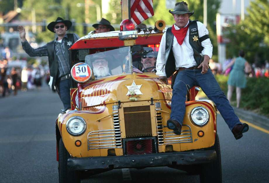 "Members of the Lake City Vigilantes bounce along on their 1949 International ""Paddy Wagon"" during Lake City's 70th annual Pioneer Days. The annual festival includes a street fair, salmon bake and parade. Photographed on Saturday, August 4, 2012. Photo: JOSHUA TRUJILLO / SEATTLEPI.COM"