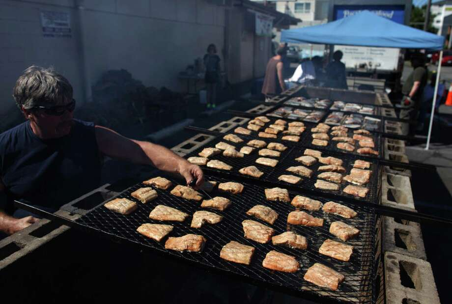 Salmon is grilled over an alder fire in front of the Lake City Community Center during Lake City's 70th annual Pioneer Days. The Salmon Bake is a fund-raiser for the community center. The annual festival includes a street fair, salmon bake and parade. Photographed on Saturday, August 4, 2012. Photo: JOSHUA TRUJILLO / SEATTLEPI.COM