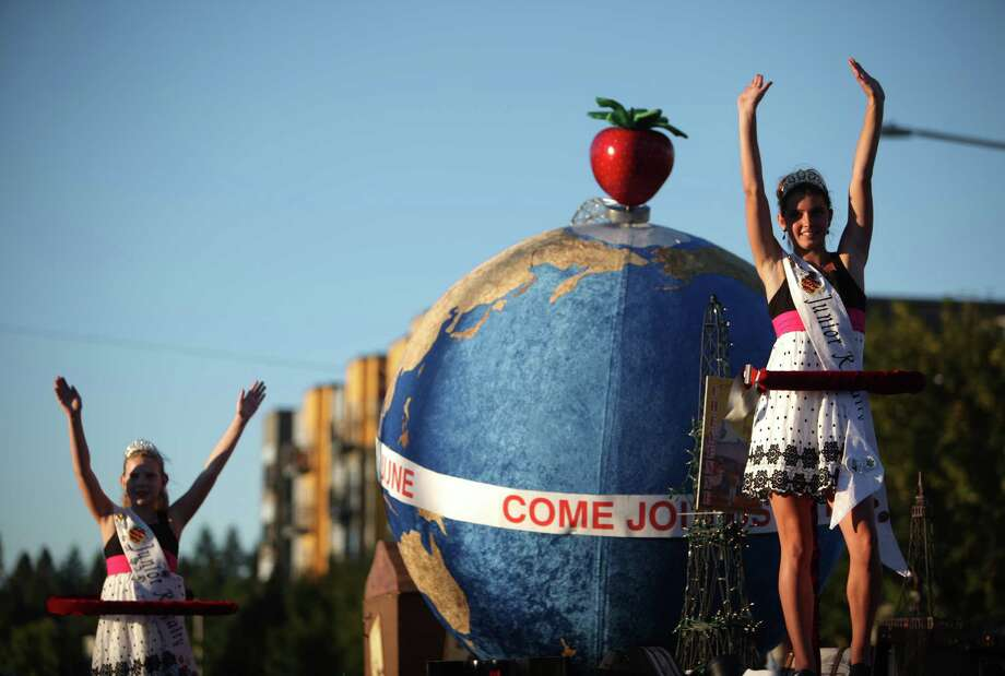 Participants ride on the Marysville Strawberry Festival float during Lake City's 70th annual Pioneer Days Grand Parade. The annual festival includes a street fair, salmon bake and parade. Photographed on Saturday, August 4, 2012. Photo: JOSHUA TRUJILLO / SEATTLEPI.COM