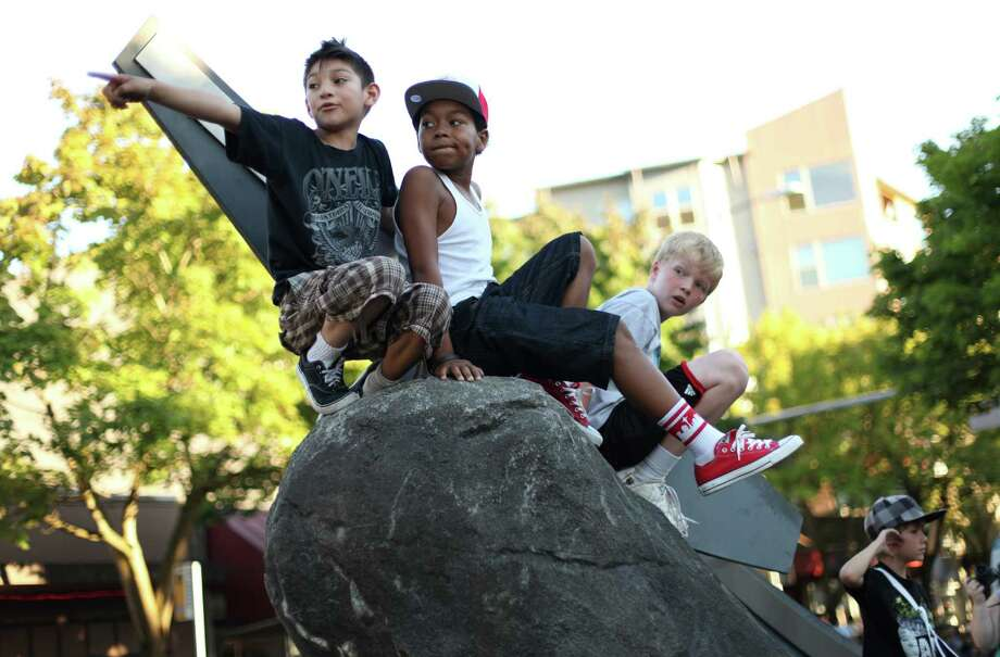 Danny Ruiz, 10, left, and O'Shae Barquet, 10, have a prime spot on Lake City Way atop a sculpture to to see the Pioneer Days Grand Parade during the 70th annual Pioneer Days celebration. The annual festival includes a street fair, salmon bake and parade. Photographed on Saturday, August 4, 2012. Photo: JOSHUA TRUJILLO / SEATTLEPI.COM