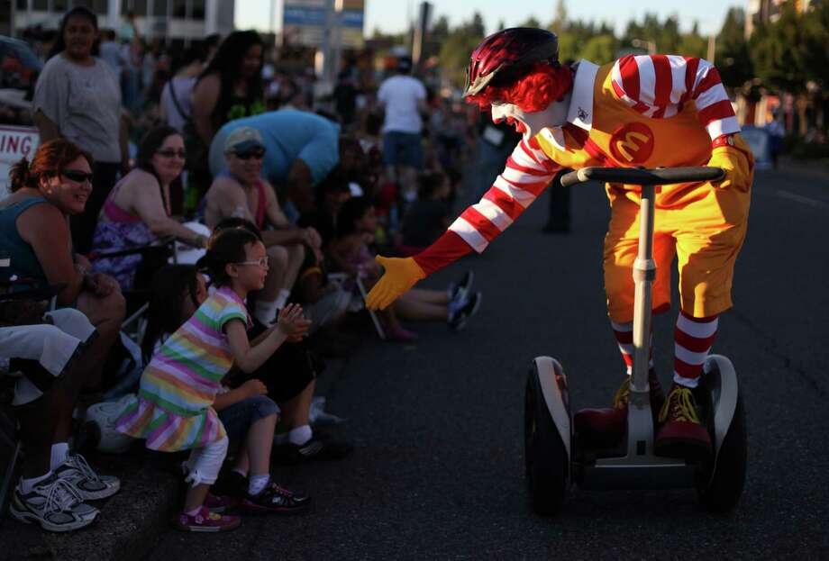 Spectators get a visit from Ronald McDonald during Lake City's 70th annual Pioneer Days. The annual festival includes a street fair, salmon bake and parade. Photographed on Saturday, August 4, 2012. Photo: JOSHUA TRUJILLO / SEATTLEPI.COM
