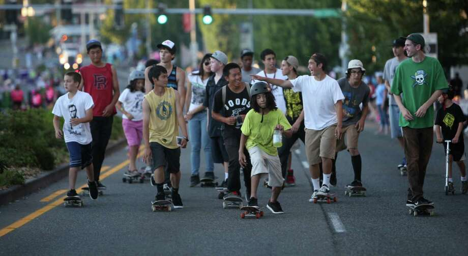 Skateboarders ride along Lake City Way in the Grand Parade during Lake City's 70th annual Pioneer Days. Skaters and parents in the community are working to build a skate park in Lake City and came out in force for the festival. The annual festival includes a street fair, salmon bake and parade. Photographed on Saturday, August 4, 2012. Photo: JOSHUA TRUJILLO / SEATTLEPI.COM