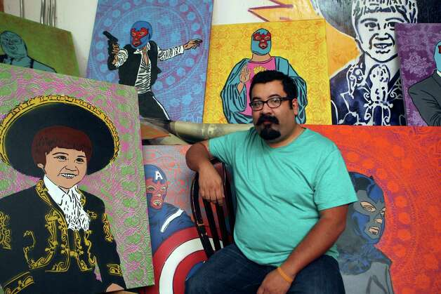 David Almaguer is an artist who specializes in spray painting onto a canvas over stencils he's created. His latest series portrays him dressed as various childhood heroes, from Jesus to Batman, wearing a lucha libre mask. Photo: Helen L. Montoya, San Antonio Express-News / ©SAN ANTONIO EXPRESS-NEWS