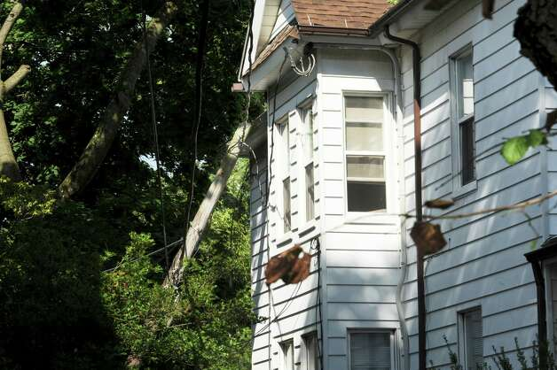 A telephone pole fell on a house, 271 Sound Beach Ave., in Old Greenwich, Monday, Aug. 6, 2012. A violent storm struck Greenwich Sunday night, knocking down trees that damaged homes in Old Greenwich. Photo: Helen Neafsey / Greenwich Time