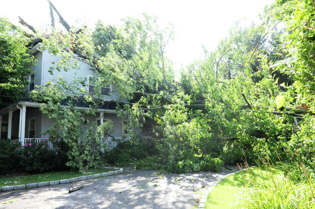 A tree on a house at 12 Wahneta Road in Old Greenwich, Monday, Aug 6, 2012. A violent storm struck Greenwich Sunday night, knocking down trees that damaged homes in Old Greenwich. Photo: Helen Neafsey / Greenwich Time